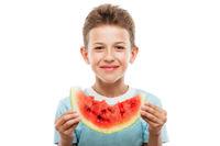 Handsome smiling child boy holding red watermelon fruit slice