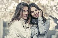 Two young fashion teen girls walking in autumn park