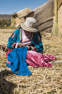 Unrecognizable woman in national costume of Indian Uros is embroidering a decorative pillow