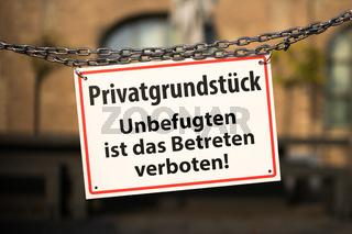 warning sign with german text 'Privatgrundstueck - Unbefugten ist das Betreten verboten' ( private property - no trespassing)