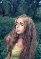 Long haired blonde girl posing in the park looking away retro toned image