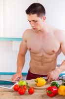 Junger Mann Bodybuilder kochen Essen Gemüse Mittagessen Internet Tablet gesunde Ernährung