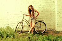 Unhappy woman posing against white wall with her urban bike, a lot of space for text, cros processed color shift