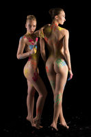 Two nude girls with colorful bodyart isolated shot