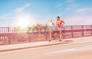 smiling couple running at summer seaside