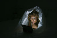 Excited woman under blanket with tablet