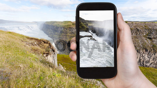tourist photographs Gullfoss waterfall in Iceland