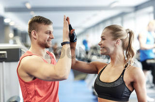 smiling man and woman doing high five in gym