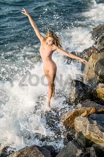 Ballerina posing on seashore
