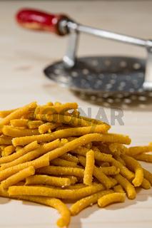 Closeup of Passatelli original Italian pasta over a wooden background
