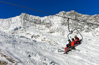 Skiers on a chairlift against the Fee Glacier and the peak Dom, skiing area Saas-Fee,Switzerland