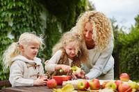 Mutter und Kinder schälen Äpfel