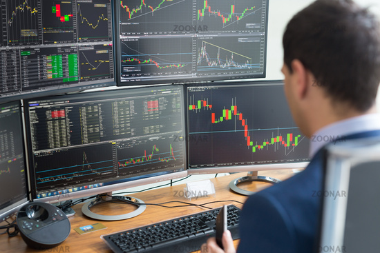Over the shoulder view of computer screens and stock broker trading online.