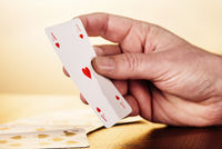 Hand with ace of hearts playing card