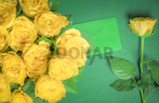 Yellow roses and a green envelope