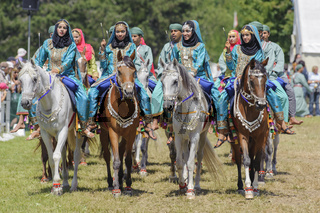Members of the Arab show group 'Royal Cavalry of Oman' ride in magnificent robes on Arab horses