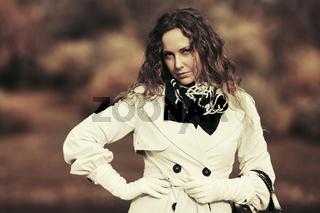 Beautiful fashion woman in white coat walking outdoor