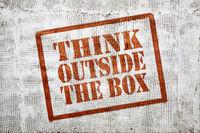 think outside the box graffiti on stucco wall
