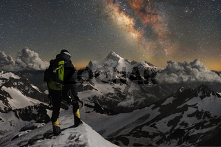 Night photo climber stands on top of a mountain in the snow and looks at the surrounding mountains over which the starry sky and the milky way