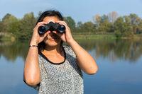 Woman looking through binoculars at waterfront