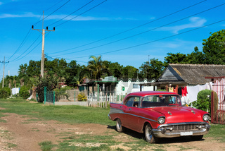 Amerikanischer roter Oldtimer parkt am Strassenrand in Matanzas Cuba - Serie Cuba Reportage