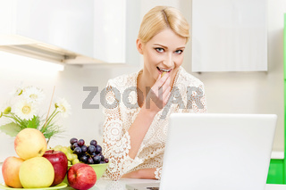 Beautiful young woman using her laptop computer in the kitchen