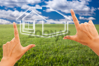 Female Hands Framing House Over Grass Field and Sky