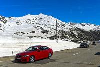 PKWs parken an einer hohen Schneemauer auf dem Gotthardpass
