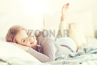happy young woman lying in bed at home