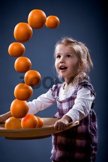 girl balancing oranges