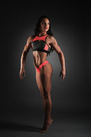 Bodybuilding. Woman posing showing her muscles