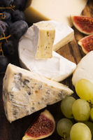 Assortment of cheese with fruits and grapes