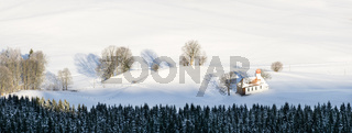Beautiful chapel in lovely rural countryside on snowy winter sunrise seen from above. Weitnau, Allgau, Bavaria, Germany.