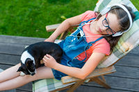 Girl resting in the garden with her dog and listening to music