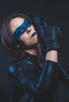 Spy, Brunette girl dressed in leather and latex fitted with pistol on blue background
