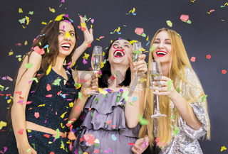 Three young woman having fun with champagne