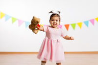 happy baby girl with teddy bear on birthday party