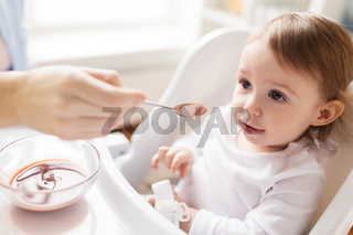 mother feeding baby with puree at home