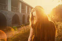 Young woman hide her face with long blond hair backlit by sun selective focus toned image, sun flares