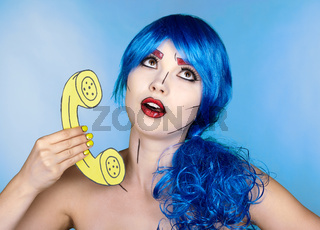 Portrait of young woman in comic  pop art make-up style.  Female in blue wig on blue background calls by phone