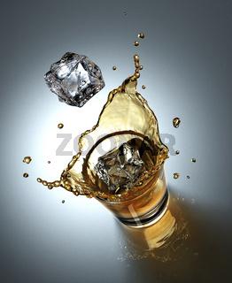 ice cube splashing in a glass full of liquid