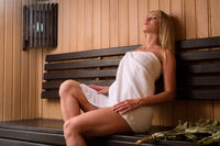 Young blonde wrapped in a towel relaxing in sauna