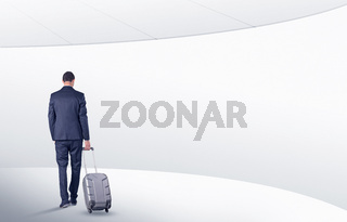 Businessman with suitcase walking in waiting room