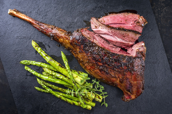 Barbecue Haunch of Venison green asparagus as close-up on a slate slab