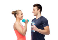 sportive man and woman with dumbbell and water