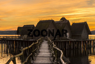 Wooden bridge and houses suspended over lake water