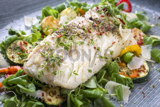 Fried cod fish fillet with lettuce and vegetable as close-up on a plate