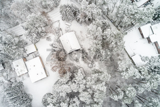 Aerial photo in a vertical perspective, winter landscape with single-family houses in the forest during the winter with a lot of snow in the forest and on the roof, aerial view