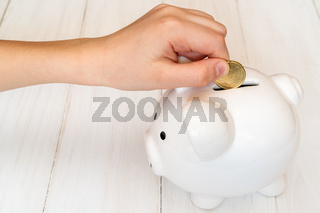 Child's hand putting a coin into piggy bank