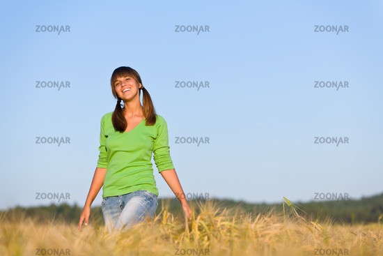 Young woman in sunset corn field